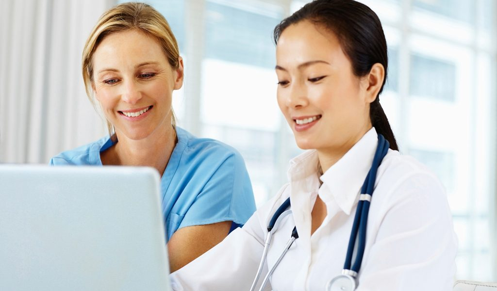 Female doctors using a laptop together